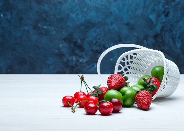 Scattered cherries with strawberries and green plums from a basket Free Photo