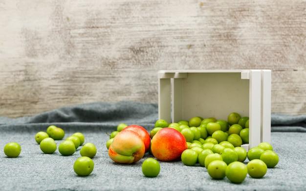 白い長方形のボウルに散りばめられた緑の梅とグレーと汚れたおいしい桃の側面図 無料写真