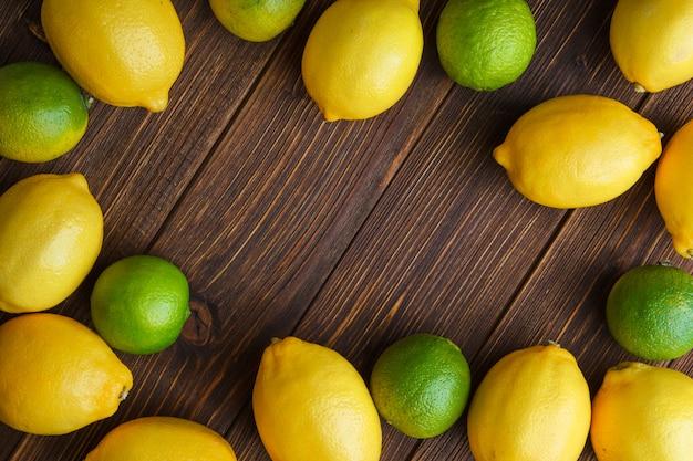 木製のテーブルの上に平らに横たわるライムと散乱レモン 無料写真