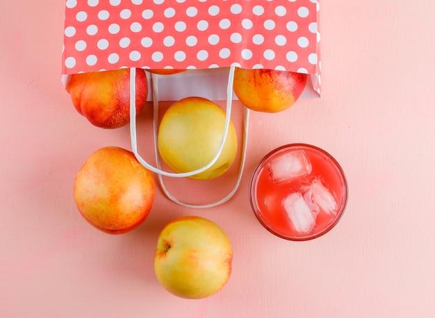 ピンクのテーブルの紙袋からジュースを散らしたネクタリン、フラットレイ。 無料写真