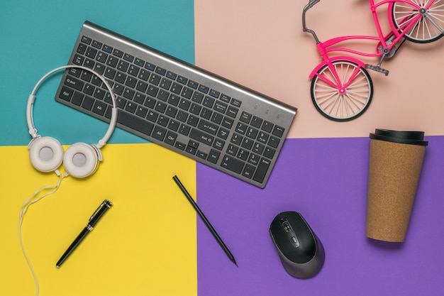 화려한 테이블 키보드, 헤드폰 및 자전거 장난감에 흩어져 있습니다. 디자이너의 직장. 프리미엄 사진