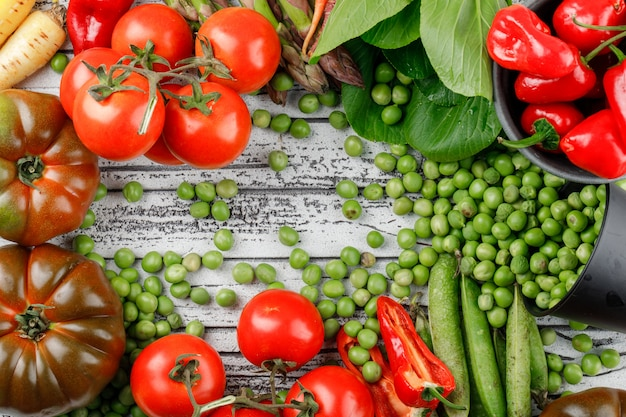 Scattered peas from a bucket with peppers, tomatoes, bok choy, green pods, asparagus, carrots flat lay on a wooden wall Free Photo