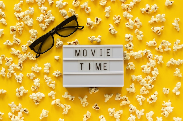 Scattered popcorn, 3d glasses and lightbox text movie time. top view template Premium Photo