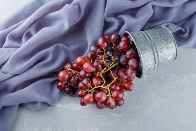 石膏と織物のミニバケツから散りばめられた赤いブドウ、 無料写真