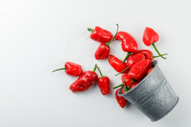 Scattered red peppers from a mini bucket on a white wall. top view. Free Photo