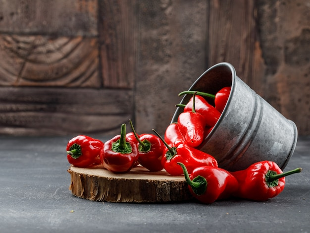 Scattered red peppers from a mini bucket with wooden piece side view on grey and stone tile wall Free Photo
