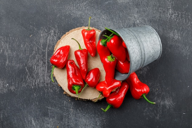 Scattered red peppers from a mini bucket with wooden piece top view on a grungy grey wall Free Photo