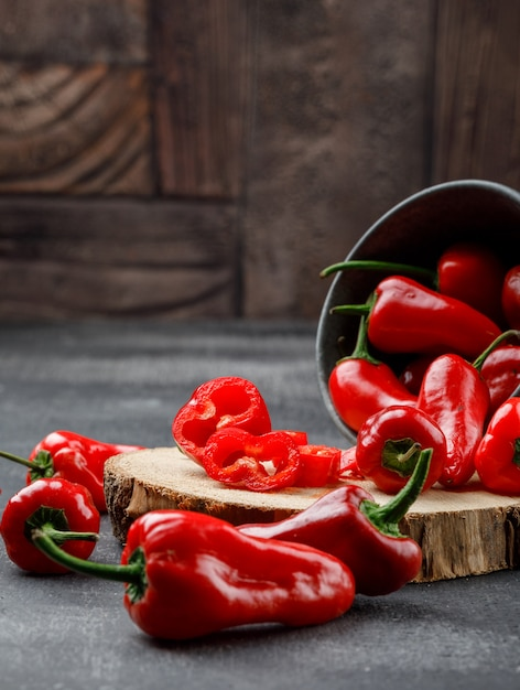 Scattered red peppers with wooden piece in a mini bucket on grey and stone tile wall, high angle view. Free Photo
