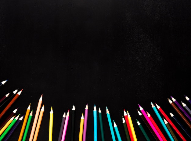 Scattered sharpened color pencils placed in bottom of black background Free Photo