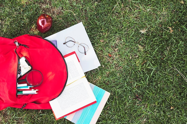Scattered stationery from red backpack on grass Free Photo