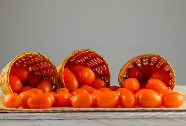 灰色と木製のスペースにピクニック布の側面図が付いているバスケットからの散乱トマト 無料写真