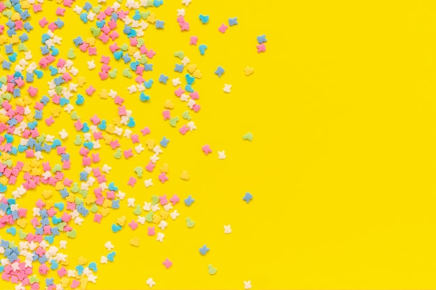 Scattering multicolored confectionery topping dressing on yellow paper. festive background Premium Photo