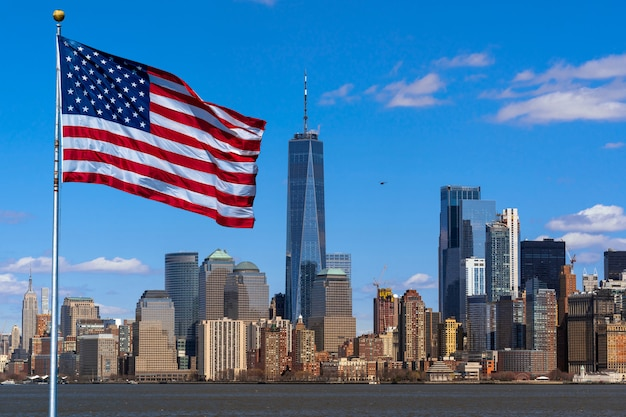 Scene of flag of america over new york cityscape river side which location is lower manhattan Premium Photo