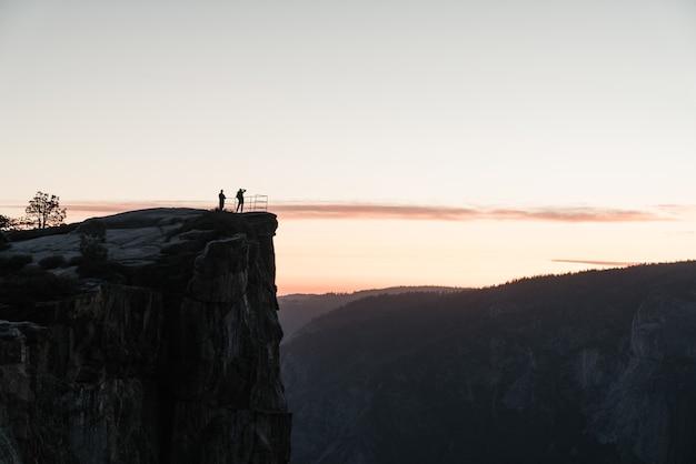 自然の美しさを眺めながら、岩の上に立つ人々の風景 無料写真