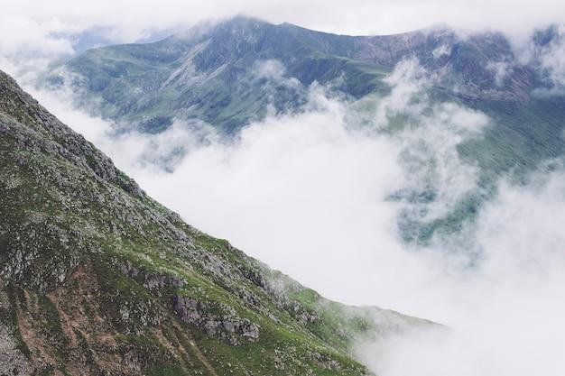 緑の景色の真ん中にある山から出てくる煙の風景 無料写真