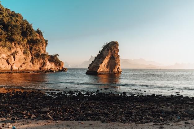 Scenario del tramonto con una bellissima formazione rocciosa sulla spiaggia di rio de janeiro, brasile Foto Gratuite