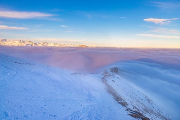 Scenic alpine landscape, clouds on the valley arisign mountain peaks sunset light, winter snow. Premium Photo