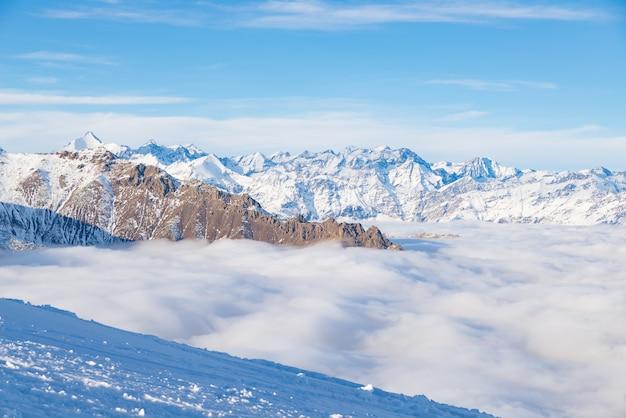 Scenic alpine landscape, clouds on the valley arisign mountain peaks sunset light Premium Photo
