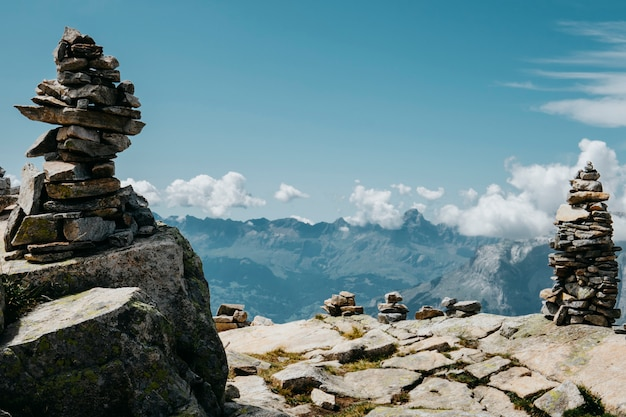 Scenic alps mountain panorama. journey travel trek and real life concept. beautiful nature. rest in the mountains. autumn in alps in green and white colors. rock totems Premium Photo