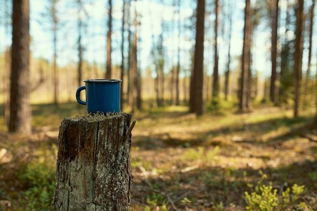 Vista panoramica dell'escursionismo smaltato tazza di tè sul moncone in primo piano con alberi di pino e cielo blu sullo sfondo. Foto Gratuite