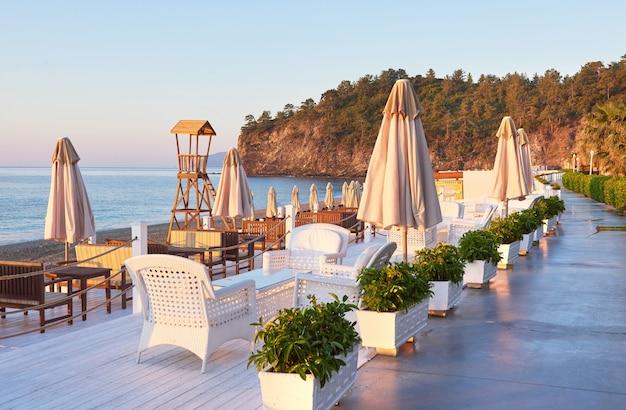 サンベッドのある砂浜のプライベートビーチと、海と山のパラソカミーの美しい景色。リゾート。 無料写真
