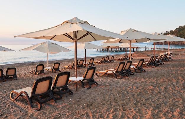 サンベッドとパラソルが海と山に向かって開いているビーチの砂浜の美しい景色。アマラドルチェヴィータラグジュアリーホテル。リゾート。ケメロボ・ケメル。七面鳥 無料写真