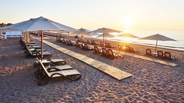Scenic view of sandy beach on the beach with sun beds and umbrellas open against the sea and mountains. hotel. resort. tekirova-kemer. turkey Free Photo