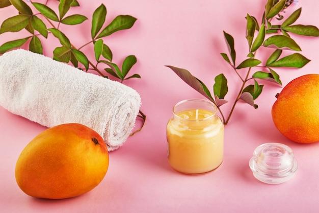 ピンクのスペースにマンゴーの香りと緑の葉が付いたスパと家庭用の香り付きキャンドル。 Premium写真
