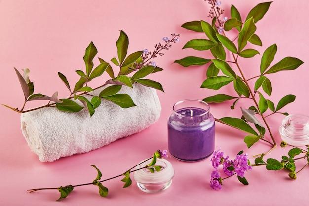 ピンクのスペースにラベンダーの香りと緑の葉が付いたスパと家庭用の香りのキャンドル。 Premium写真