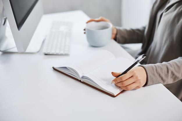 スケジュールは私の一日を維持するのに役立ちます。コンピューターの前で働いて、ノートに書いて、コーヒーを飲む女性のショットをトリミングしました。実業家は日中彼女の会議の計画を立てる 無料写真