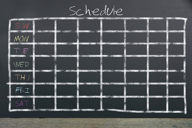 Schedule with grid time table on black chalkboard Premium Photo