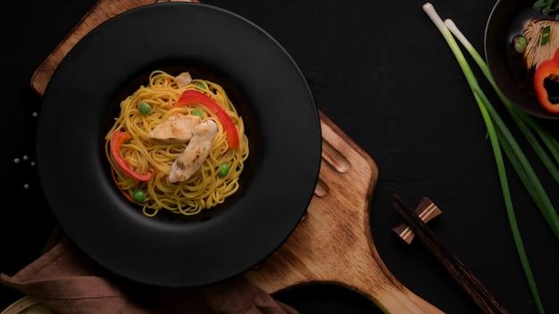 Schezwan noodlesまたはchow meinのオーバーシュート、野菜、チキン、チリソース添え Premium写真