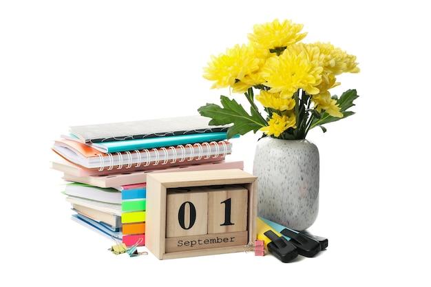 Школьные принадлежности, деревянный календарь и цветы, изолированные на белом фоне Premium Фотографии