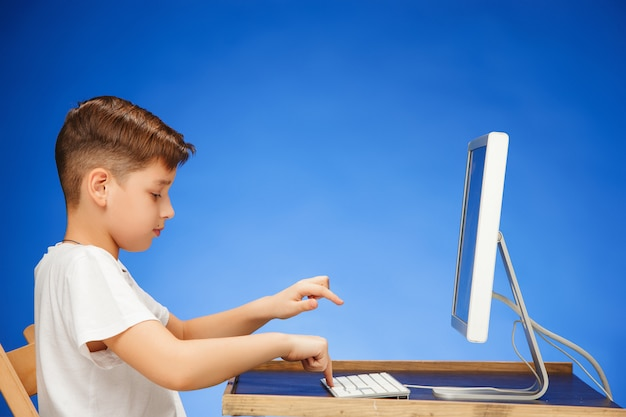School-age boy sitting in front of monitor laptop Free Photo