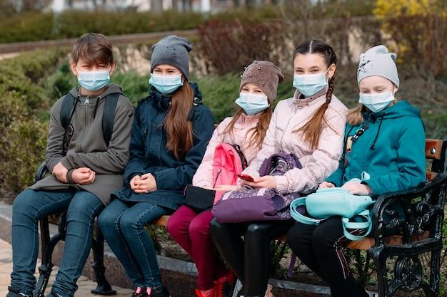 医療マスクの学齢期の子供たちはベンチに座っています。 Premium写真