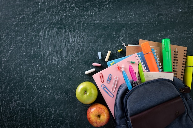 School backpack and school supplies with chalkboard background Premium Photo
