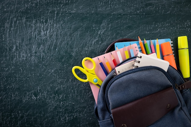 School backpack and supplies with chalkboard. back to school concept. Premium Photo