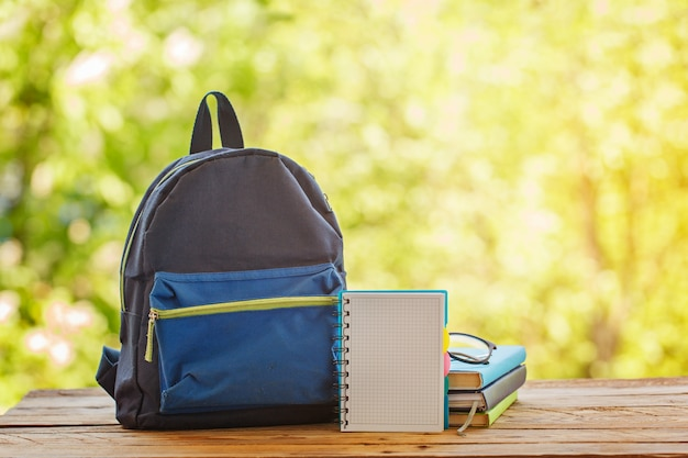 School backpack with books on wooden table and nature background Premium Photo