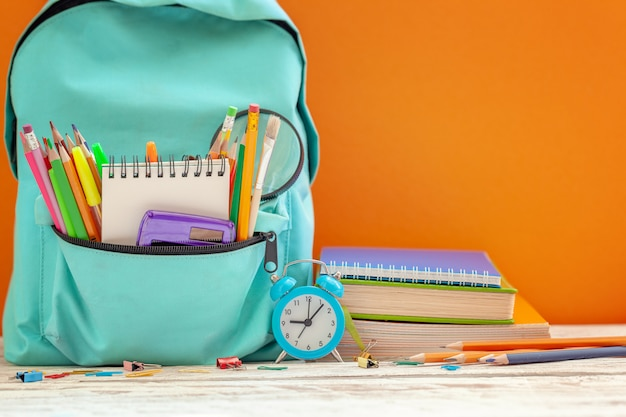School backpack with different supplies and alarm clock on orange background. Premium Photo