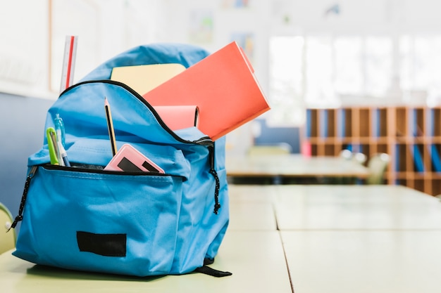 School bag with various tools on desk Free Photo