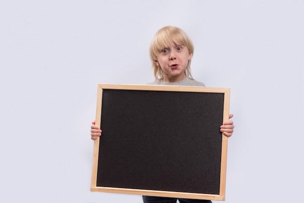 白い背景の上の少年の手の中の教育委員会。スペースをコピーします。テンプレート。モックアップ Premium写真