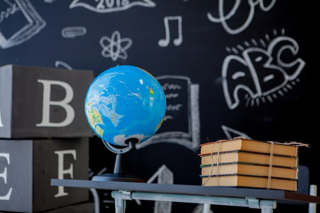 School books and world globe on school desk Premium Photo
