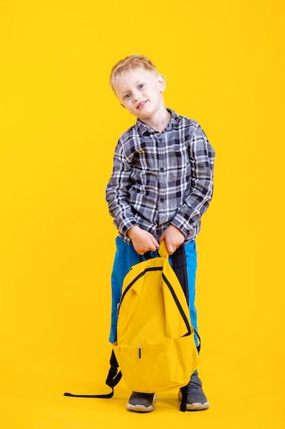 School boy holding bag smiling Premium Photo