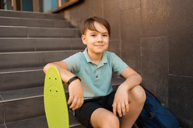 Школьник в синей рубашке поло сидит на лестнице с синим рюкзаком и зеленой копейкой Бесплатные Фотографии