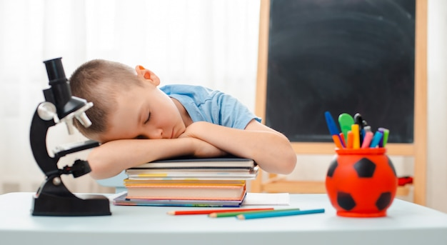 School boy sitting home classroom lying desk filled with books training material schoolchild sleeping lazy bored Premium Photo