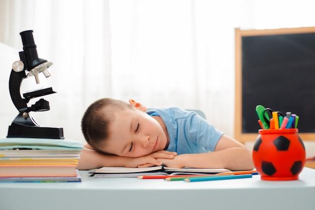 School boy sitting home classroom lying desk filled with books training material schoolchild sleeping Premium Photo