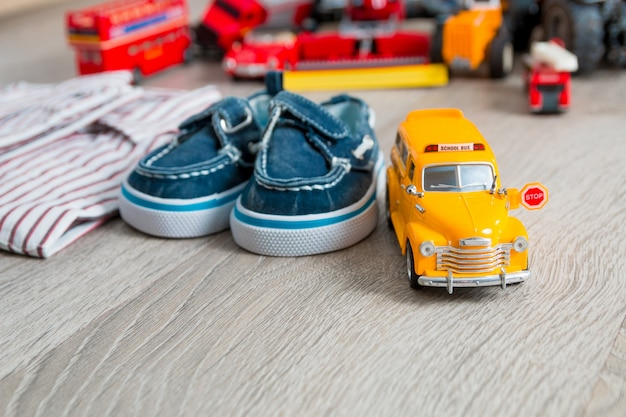 School bus toy near shirts and blue boat shoes on grey wooden surface boy outfit close up Premium Photo