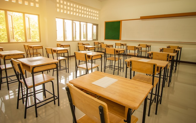 School classroom with test exam paper on desks chair wood Premium Photo