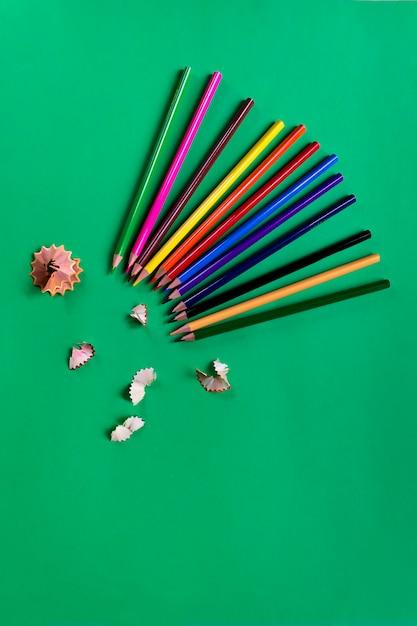 School colored pencils on a paper dark green background. school supplies. flat lay Premium Photo