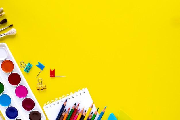 Copyspaceと黄色の背景にカラフルな文房具を学校します。 無料写真